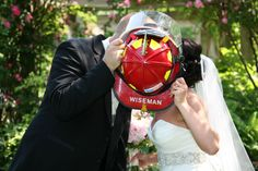 kissing behind a firemen hat  www.ronwoodphoto.com