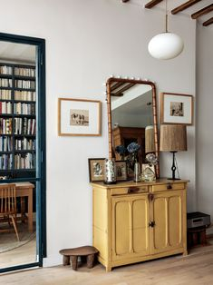 An ensemble of flea market pieces: Hermand frequents the St. Ouen Marché aux Puces. She uses African stool as low tables. The steel door frame is in a powder-coated blue to match the library. #remodelista #remodel #interiordesign #architecture #paris #interiorinspiration