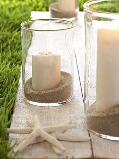 Simple beach sand candle centerpieces with hurricane vases.