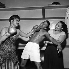 Ruth Brown, Sugar Ray Robinson, and Blanche Calloway have a good time with Ray's boxing gloves. By Bertrand Miles
