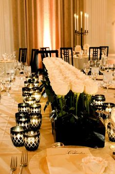 black and white indoors wedding reception  love the roses down the table