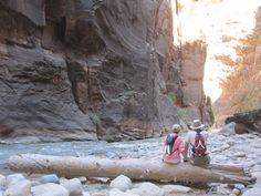 A couple resting while hiking the Narrows at Zion National Park