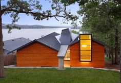 The house that Dake-Wells Architecture designed for Cory and Kerry Watts in the Ozarks in southwestern Missouri is defined by subtle nods to its lakeside setting, such as an elevated wooden plank that carries visitors over a bed of river rock to the north entrance.  Courtesy of: Gayle Babcock, Architectural Imageworks LLC