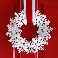 Glue dollar store snowflakes to a flat wreath and hang with ribbon.