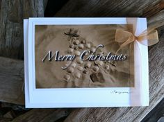 """This card set consists of six cards and envelopes featuring the """"Merry Christmas"""" scallop shell beach tree holiday card. Hand-created cards made with original photographs are hand-signed and blank inside. Card stock and envelopes are white. Cards measure 5"""" x 6.5"""". Card sets are packaged in a sealed, clear sleeve and adorned with a gold organza bow tie.  https://www.etsy.com/listing/166508088/merry-christmas-card-set-by-the-coastal?ref=shop_home_active"""