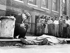 Death in a Bronx Gutter - While stunned spectators look on, a policeman makes notes over the body Eugene Giannini, a hoodlum w/ a long police record.  Shot in the back of the head and dumped on the street. (1952)