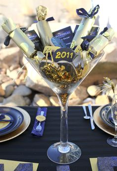 GREAT IDEA! Gold, glittery sparkles are sprinkled into the bottom of a Giant-sized Martini Glass that is filled with little, gold-wrapped noise crackers and yummy chocolates; An alternative could be regular-sized champagne flutes filled with each person's cracker or noisemaker and confetti. *^-^* Happy New Year! ~ Love, B33Happy Honey
