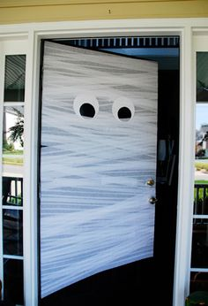 Mummify your front door in just five minutes with some crepe paper, construction paper, and tape.