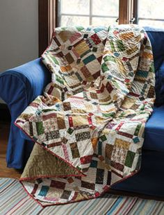 """Dig into your pile of scraps for this colorful quilt. """"Flippy corners"""" make quick work of the triangles on each small square on this fat quarter friendly quilt by Mark Lipinski named What's the Point."""