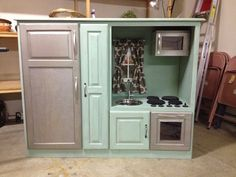 """A play kitchen... nice large """"stainless"""" fridge and sink and stove... and what's that I see?  A slide out pantry?  (I'm going to look to find what that is (maybe it originally held dvd's or vhs tapes?)  #upcycled #entertainment #center or #armoire"""
