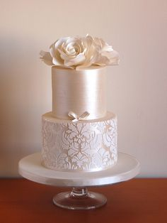 Ganached cake/sharp edge technique with sugar flowers, pearlized finish and stenciling. I learned these techniques from Faye Cahill in Sydney Australia. If you can ever get the good fortune to take a class there, I cannot recommend it enough.