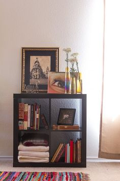 This Ikea shelf has been with me a long time. It's so basic and fits into any nook. The colorful rug is from World Market. The flower vases are vintage – I love decorating with vintage glassware in interesting tones and shapes. I am also very into brass right now; I buy a lot of vintage brass items for my shop and I have a few little things that I love in my home, like this swan mail rack. The painting is of Madrid's Gran Via. My parents bought it for me in Spain when I was 18.