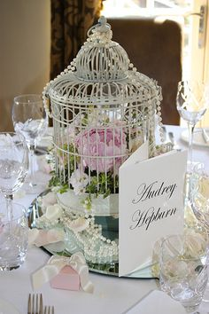 Movie Star Table Names: Instead of numbers! Centerpiece: Pearl draped bird cage filled with flowers & moss, set upon a large round mirror.