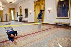 "First Lady Michelle Obama participates in a potato sack race with Jimmy Fallon in the East Room of the White House during a ""Late Night with Jimmy Fallon"" taping for the second anniversary of the ""Let's Move!"" initiative, Jan. 25, 2012. (Official White House Photo by Chuck Kennedy)"