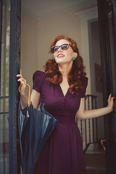 From her gorgeous red curls to the cut and perfect plum hue of that dress, I adore her lovely vintage inspired look. #fashion #dress #redhead #red #hair #woman #vintage #umbrella
