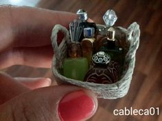 I made this miniature basket of perfume bottles using ideas I saw on Pinterest. I used hemp and craft glue to make the basket using a coil method around a square nail polish bottle.  I made the bottles from plastic and glass beads. I got creative and used an orphaned earring for one top and the jack from a broken power cord for another.  -Carla