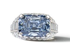 The extraordinarily rare, fancy deep-blue diamond appears in an unusual east-west setting, surrounded by a mount of pavé-set brilliant-cut diamonds and baguette-cut diamonds.