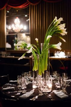 Simple wedding centerpiece: Tall white calla lilies spilling out of clear glass vases. Dream A Little Dream Events.