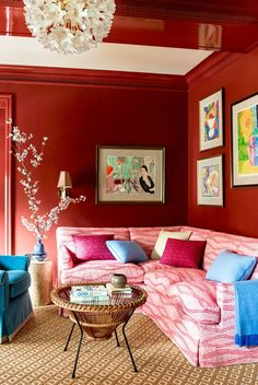 red walls, pink patterned sofa, blue pillows and chair