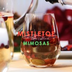 Cheers! Serve up this festive cocktail for the holidays. Mistletoe Mimosas made with sparkling apple cider, Proscecco and chilled fruit are a signature cocktail that's merry and bright. #cocktails #holidaydrinks #entertaining #partydrinks #Christmas
