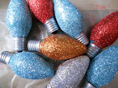 Old, burnt out Christmas lights dipped in glue then glitter. Pile in a big clear jar. I love this idea.