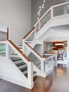 Picturesque Three-Storey House Building with Natural Landscape: Attractive Staircase With White Handle And Modern Hanging Lamps In Modern El...