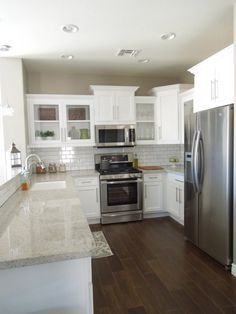 Small bright kitchen ...varied cabinet heights, molding, open glass fronts, bar counter, subway tile, dark floor...