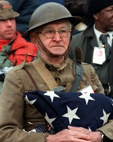 """Joseph Ambrose, a then-86-year-old World War I veteran, attends the dedication day parade for the Vietnam Veterans Memorial in 1982, holding the flag that covered the casket of his son, who was killed in that war."""