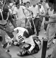 """Then 18-year-old Keshia Thomas of Ann Arbor shields a man wearing a Confederate T-shirt from an angry crowd during a Ku Klux Klan rally on June 22, 1996, outside Ann Arbor's city hall. Thomas, who won national attention for her act, later said: """"People don't have to remember my name. I just want them to remember that I did the right thing."""""""