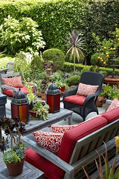 FANTASTIC!!! Outdoor Entertainment Spaces. I love the burgundy lanterns, the cool grey color of the furniture frame & the tasteful pops of red fabric highlights all the beautiful shades of green in the surrounding plants & hedges