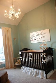 Nursery with soft green blue walls and yellow curtains