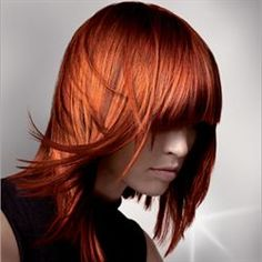 Medium length straight vibrant red layered haircut with blunt cut bangs hairstyle