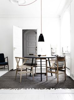white walls  wooden table and chairs grey door grey rug pendant lighting rocker simplistic neutral