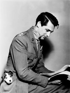 Cary Grant reading with a puppy in his pocket
