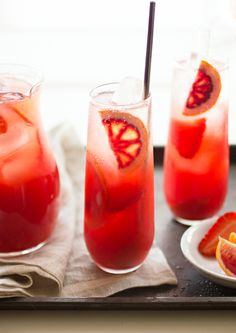 Strawberry Blood Orange Rum Punch: 3-4 medium strawberries, hulled 1 1/2 teaspoons organic cane sugar 2 ounces (1/4 cup) blood orange juice (from 1 medium blood orange) 1 ounce (2 tablespoons) meyer lemon juice (or 1/2 ounce regular lemon juice) 1/2 ounce (1 tablespoon) lime juice 1 1/2 ounces (3 tablespoons) white rum 1/2 ounce (1 tablespoon) dark rum ice about 2 ounces sparkling water strawberry and blood orange slices, for garnish. #Drinks #Cocktail