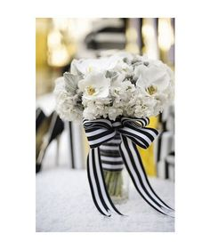 White bouquet tied with black and white striped ribbon.