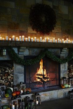 Cozy fireplace with pillars of candles across the mantle inside the Blackberry Farm barn.