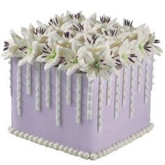 Lilies were made for the spotlight! See them take their bow on this pretty violet square cake highlighted by fondant strips on every side.