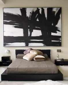 """It took me a few looks to decide I did indeed love this ... """"I wanted the bed to look like a bento box,"""" Kevin Sharkey says. A low platform bed frame stained black alongside marble-topped tables achieves the effect. An oversize graphic painting against beige walls helps furniture to feel grounded in the soaring room.""""  """""""