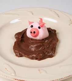 Piggie in the Mud. Chocolate pudding mud with a marshmallow pig stuck in it.