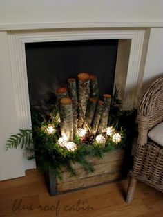 Old wood crate filled with logs, greens, pine cones, and lights.