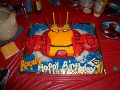 IronMan Cake: Baked 2 small round cakes and extra large cookie sheet cake. Cut, shaped, and frosted into IronMan. Colored coconut to make sky and clouds.