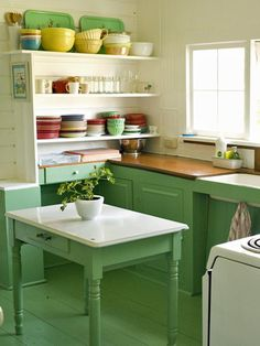 The green painted floors, kitchen table and cabinets in this coastal cottage have a vintage quality that almost has a green milk-glass quality. The open shelves display a rainbow assortment of bowls and plates. The pretty mismatched dishware adds to the casual, unfussy style you connect with a beach house.