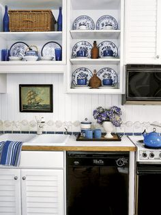 A display of blue-and-white floral plates and cobalt glasses and mugs continue a bold color scheme in this kitchen.