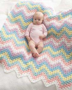 Crochet this zig-zag blanket in the rainbow colors of Bernat Giggles.