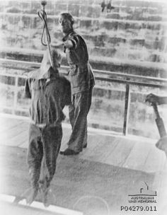 """A British officer (centre) releasing his hold on a hooded Japanese war criminal as the prisoner falls to his death. The trapdoor has just been sprung by the operator whose hands can been seen holding the release lever at right. These gallows had provision for multiple simultaneous executions (note the D-bolt shackle at top right and circle painted on the trapdoor for positioning the condemned). The photographer captioned his original print """"On the Way."""" Singapore: Changi. 1946."""