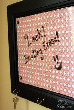 This one is made from a cabinet door, but I feel like it would be easier still to use a cheap frame, paint it a good color, screw in some hooks for keys, then put a good looking piece of scrapbook paper or fabric behind the glass.