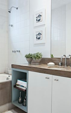 O banheiro social, com a tão sonhada banheira (Pool Shop), exibe azulejos brancos e bancada de concreto igual à da cozinha, feita sob medida pela Ornamentum. Marcenaria da EBF Armários.