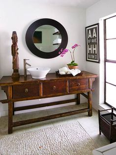 "Eclectic Simplicity - With a do-it-yourself mind-set, the owners of this small master bathroom created a personal sanctuary on a budget. This Asian butcher table, found at an antiques shop, was repurposed for the vanity. The table maintains its authenticity with a simple above-counter sink. A new mirror adds a modern touch, while a pebble-tile ""rug"" on the floor adds texture and a spa-like accent."