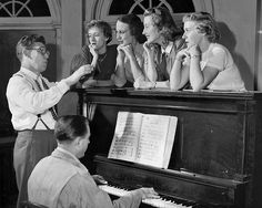 """In November 1950, Richard Walters, left, warms up Council Bluffs Civic Music singers before a rehearsal of the operetta """"Bloomer Girl."""" Babette Bronson, Luanne Bisbee, Nancy Ogren and Janet Hicks sing to the music of pianist Frank Fariday. THE WORLD-HERALD"""